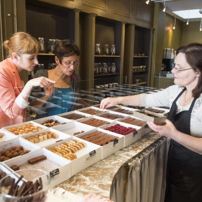 A saleswoman is helping two female clients picking chocolates in a chocolate store in Brussels, Belgium