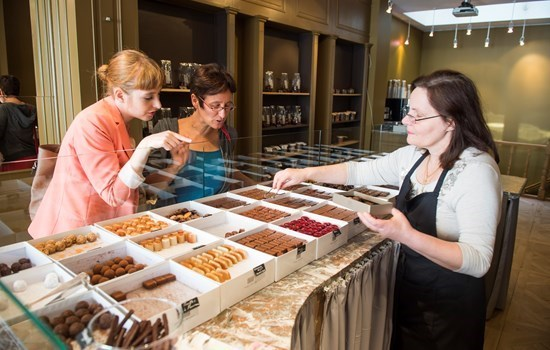 Two women choosing chocolates in a Belgian chocolate store